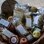 Cesto di corda e manici in legno con mele e prodotti della cascina